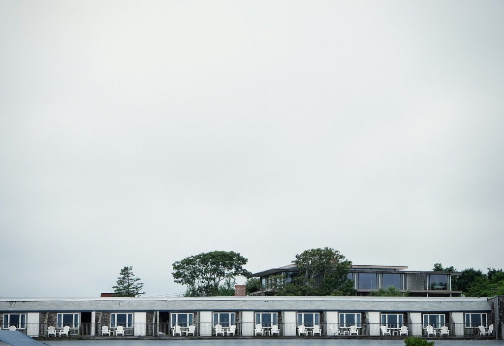 Outside view of beachside motel balconies with trees and a grey sky behind.